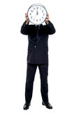 Executive holding up wall clock in front of his face Royalty Free Stock Images