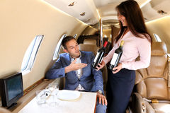 Executive jet passenger picking up the red wine Stock Photo