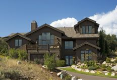 Executive luxury Log Cabin home. Executive wooden home with flag and landscape on a hill Royalty Free Stock Image