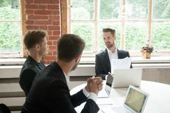 Executive male team discussing new project at meeting in boardro. Three businessmen negotiate at meeting in boardroom, art director presenting new design project Royalty Free Stock Photo