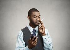Executive man holding smart phone, smoking cigarette. Phone, nic Royalty Free Stock Photos