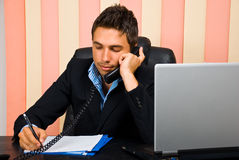 Executive man on the phone taking notes Royalty Free Stock Photos