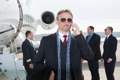 Executive manager in front of corporate jet using a smartphone Royalty Free Stock Image