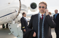 Executive manager in front of corporate jet using a smartphone. Business people and pilot in the background Royalty Free Stock Photo
