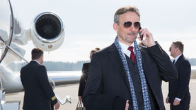 Executive manager in front of corporate jet using a smartphone Royalty Free Stock Photos