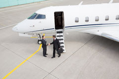 Executive manager leaving corporate jet. Handshake with pilot Stock Photos