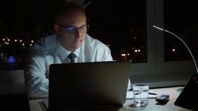 Executive manager working with laptop and drinking water in office at night. Professional corporate businessman in eyeglasses using laptop at workplace with stock footage