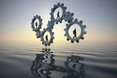 Teamwork on gears over the ocean at sunset as 3d render. Royalty Free Stock Image