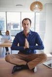 Executive meditating on desk Stock Images
