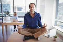 Executive meditating on desk Royalty Free Stock Photography