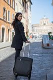 Executive and modern woman walks the street with her luggage and. Looks back Stock Photos