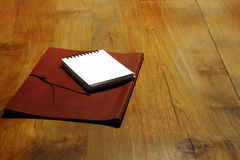 Executive notepad. An image of a leather bound document holder with a notepad on top of a timber desk royalty free stock photography