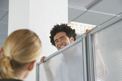 Executive Peering Over Cubicle Wall To Greet Blond Coworker. Smiling male office worker peering over cubicle wall to greet blond coworker in office Stock Image