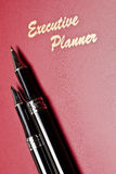 Executive Planner Slanting. Angled view of a red executive planner with slanting pens and wording Royalty Free Stock Photography