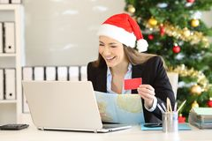 Executive planning christmas holidays at office. Joyful executive planning christmas holidays booking hotels on line at office stock photography