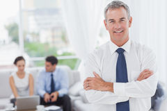 Executive posing while his colleagues are working Royalty Free Stock Photography
