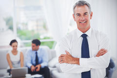 Executive posing while his colleagues are working. In cosy meeting room royalty free stock images