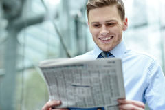 Executive posing with journal. Image of a happy corporate male reading newspaper stock photo