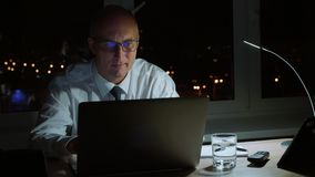 Executive professional manager smiling and workig with laptop late in the evening. Businessman in eyeglasses looking at laptop at workplace in office stock footage