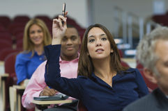 Executive Raises Hand During A Lecture. Female executive raising hand during a business lecture amid colleagues royalty free stock images
