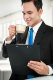 Executive reading a report while drinking Stock Photography