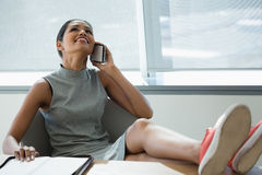 Executive relaxing at desk while talking on mobile phone Stock Photo