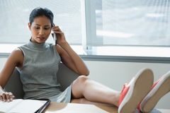 Executive relaxing at desk while talking on mobile phone Royalty Free Stock Image