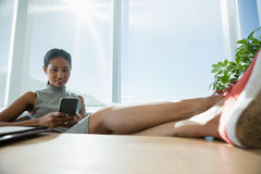 Executive relaxing at desk while using mobile phone Stock Photos