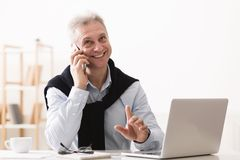Executive senior businessman consulting clients, working on laptop. At home office stock photography