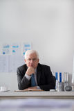 Executive senior businessman. Portrait of executive senior businessman sitting at his workplace and looking at the camera Royalty Free Stock Photography