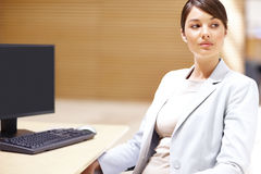Executive sitting at her desk and looking away Royalty Free Stock Photo