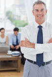 Executive standing on foreground with colleagues on background Stock Photo