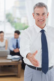 Executive standing on foreground holding out his hand Royalty Free Stock Image