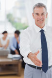 Executive standing on foreground holding out his hand to camera Royalty Free Stock Images
