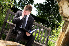 Executive Stress. A young executive businessman in a dark pinstripe suit sitting on a garden bench next to a fountain with an open black folder on his lap and royalty free stock images