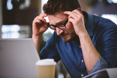 Executive suffering from headache at office. Young male executive suffering from headache while working at office Royalty Free Stock Image