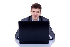 Executive in suit behind desk with laptop Stock Images