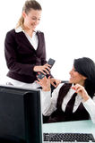 Executive taking phone receiver from her secretary stock photos