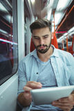 Executive using digital tablet travelling in train Stock Photos