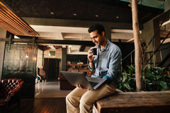 Executive using laptop during coffee break. Shot of young man sitting relaxed looking at laptop and having coffee. Male executive using laptop during coffee royalty free stock photography
