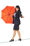 Executive  walk on tightrope with umbrella. Beautiful  executive woman walking on a tight rope and holding her equilibrium with a red umbrella isolated on white Royalty Free Stock Photography