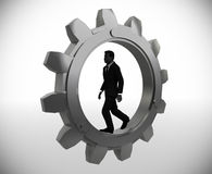 Executive walking inside a gear. An executive walking inside a gear demonstrates his talent and effectiveness Royalty Free Stock Images
