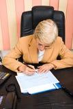 Executive woman financial analyst. Executive senior woman financial analyst writing on graphs,check also stock photo