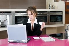 Executive woman in kitchen coffee looking laptop Stock Photo