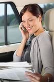 Executive woman manager sitting in car calling. Attractive executive businesswoman sitting in car calling phone checking newspapers Royalty Free Stock Photo