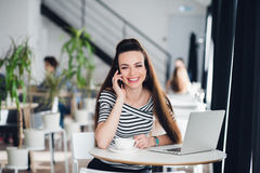 Executive woman smiling and working online with a laptop while talking on the phone in a cafe. Royalty Free Stock Photos