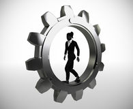 Executive worker walking inside a gear. An executive worker walking inside a gear demonstrates her talent and effectiveness Royalty Free Stock Photos
