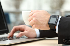 Executive working with laptop and smart watch Stock Photography