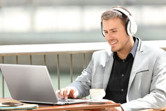 Executive working on line in a coffee shop. Portrait of an executive wearing headphones working on line sitting in a coffee shop Royalty Free Stock Photos