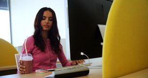 Executive working on personal computer while having milkshake. In office stock video